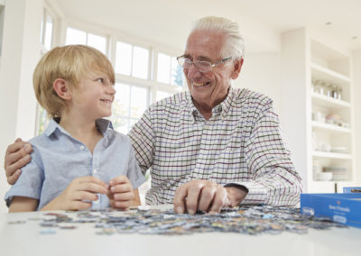 Senior man and grandson doing a jigsaw puzzle